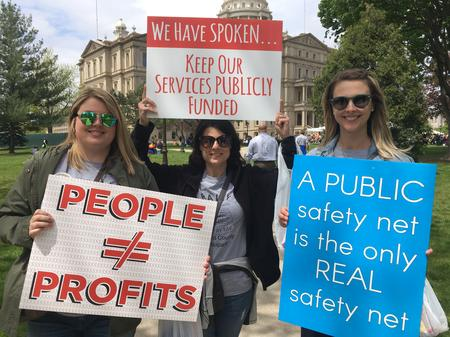 Mental health administrators Nicole Lawson, Christina Nicholas, and Jillian Trumbell demonstrate at the Michigan Capitol Cheyna Roth/MPRN