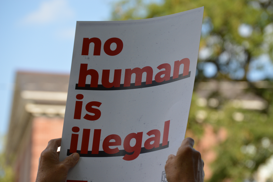 "A protester holds up a sign that reads ""no human is illegal"" at a rally in Southwest Detroit on Tuesday.Jake Neher/WDET"