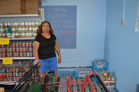 Rev. Roslyn Bouier stands in front of the water station at the Brightmoor Connection Food Pantry in Detroit. Jake Neher/WDET