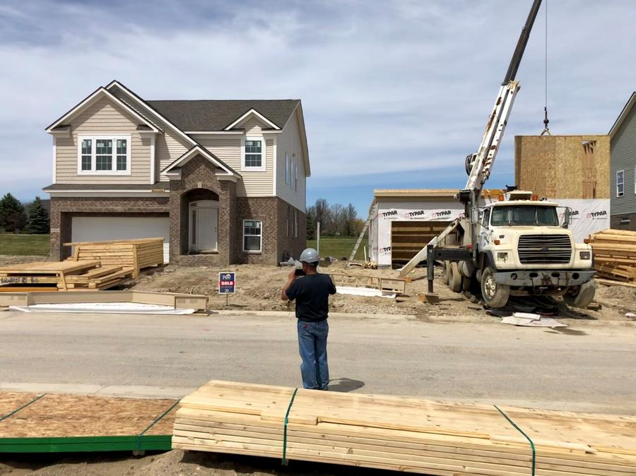 A contractor takes pictures of a home in the midst of construction.Eli Newman / WDET