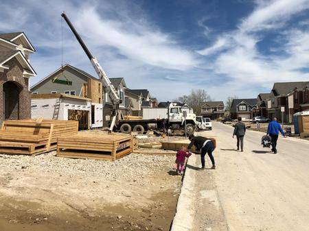 "A family walks down Shoreline Drive at ""The Landings"" subdivision development in 2019.Eli Newman / WDET"