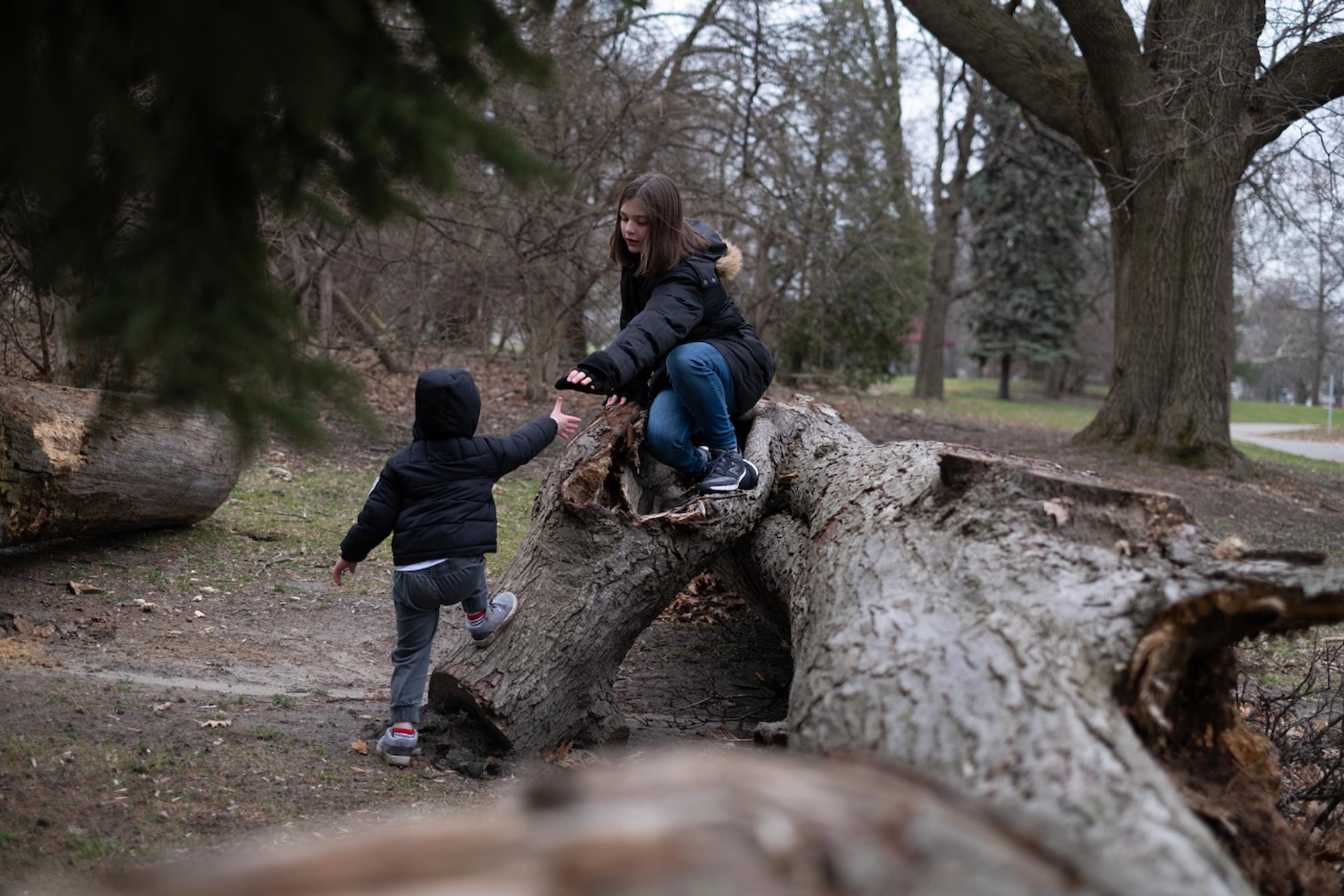 Aniela lends a hand to Emanuel as he climbs up on a log to walk across it together with his sister.Taken by Erik Paul Howard for WDET