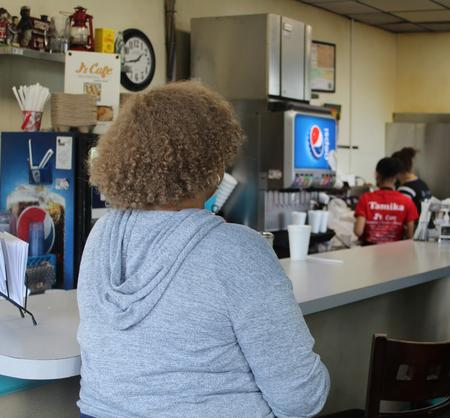 Tenecia Johnson from DEGC stops by J's Cafe to tell them about the Restaurant Revitalization Fund.  Laura Herberg / WDET